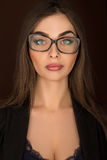 Stående av en affärskvinna med exponeringsglas och en svart dräkt Arkivfoton