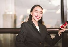 Stående av en affärskvinna som använder en mobiltelefon som ser kameran Royaltyfri Foto