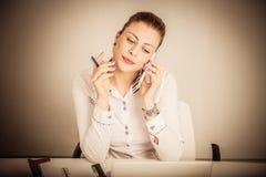 Stående av en affärskvinna som använder smartphonen på skrivbordet i royaltyfri fotografi