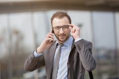 Stående av en affärsman på gatan, medan tala på hans sma Arkivfoton