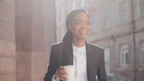 Stående av en allvarlig afrikansk amerikanaffärskvinna i en dräkt som går runt om staden och dricker kaffe Begrepp arkivfilmer