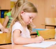 Stående av en allvarlig flicka som skriver i en skrivbok under Royaltyfri Bild