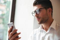Stående av en allvarlig ung affärsman i glasögon arkivfoto