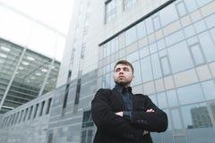 Stående av en allvarlig ung man med ett skägg i en dräkt mot bakgrunden av modern arkitektur away look Arkivfoton