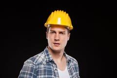 Stående av en arbetare med den gula hjälmen på huvudet royaltyfri fotografi