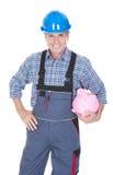 Stående av en arbetare som rymmer Piggybank Royaltyfri Foto