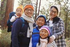 Stående av en asiatisk familj av fem i en skoginställning royaltyfri foto