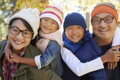 Stående av en asiatisk familj med två ungar som piggybacking föräldrar Royaltyfri Foto