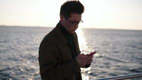 Stående av en attraktiv caucasian man i brunt lag och stilfulla exponeringsglas genom att använda smartphoneatt smsa eller rengör lager videofilmer
