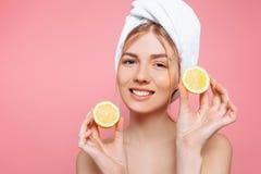 Stående av en attraktiv gladlynt kvinna med en handduk som slås in runt om hennes huvud som rymmer citronskivor över rosa bakgrun royaltyfri bild