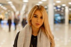 Stående av en attraktiv gullig ung blond kvinna med sexiga kanter med härliga gråa ögon i ett lag i en tappninghalsduk inomhus arkivfoton