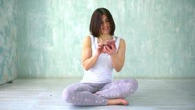 Stående av en attraktiv idrotts- kvinna Stående av en lycklig konditionkvinna som använder smartphonen i idrottshall stock video