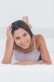 Stående av en attraktiv kvinna som kopplar av att ligga i säng Royaltyfria Foton
