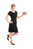 Stående av en attraktiv kvinna som rymmer en gåva Arkivfoton