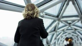 Stående av en attraktiv le affärskvinna i en korridor för affärsmitt genom att använda smartphonen som pratar med kollegor lager videofilmer