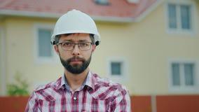 Stående av en attraktiv tekniker i en vit hjälm Det ser kameran, mot bakgrunden av en modern byggnad arkivfoton