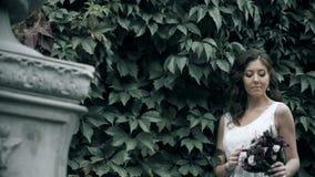 Stående av en attraktiv ung kvinna i det vita klänninganseendet i trädgård eller att parkera lager videofilmer