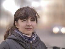 Stående av en attraktiv ung kvinna på bakgrunden av gatan royaltyfri fotografi