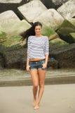 Stående av en attraktiv ung kvinna som går på stranden fotografering för bildbyråer