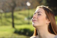 Stående av en avkopplad kvinna som djupt andas i en parkera arkivfoto