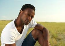 Stående av en avslappnande stilig ung man utomhus Fotografering för Bildbyråer