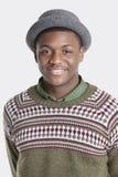 Stående av en bärande hatt för lycklig afrikansk amerikanman över grå bakgrund Royaltyfri Bild