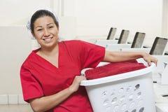 Stående av en bärande tvättkorg för lycklig ung kvinnlig anställd arkivbild