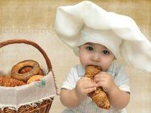 Stående av en behandla som ett barnpojke i en kockhatt med en korg av muffin och baglar royaltyfri foto