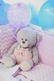 Stående av en björn för leksak för barn` s i skuggor av rosa ballonger Arkivfoton