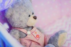 Stående av en björn för leksak för barn` s i skuggor av rosa ballonger Royaltyfria Bilder