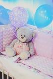 Stående av en björn för leksak för barn` s i skuggor av rosa ballonger Royaltyfria Foton