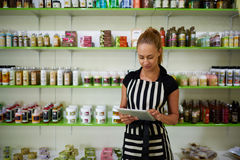 Stående av en blomstrande kvinnaentreprenör som använder handlagblocket för kontroll numret av kosmetiska produkter, Royaltyfri Fotografi