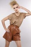 Härlig vuxen sensualitykvinna i brun klänning arkivbild