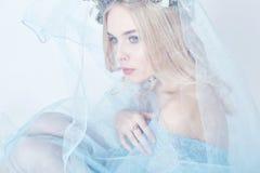 Stående av en blond kvinna med en krans på hennes huvud och en blå delikat ljus genomskinlig klänning Stora blåa ögon och härlig  Royaltyfria Foton