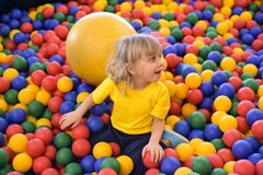 Stående av en blond pojke i en gul t-skjorta De barnleendena och lekarna i barnens lekrum Bollpöl royaltyfri foto
