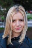 Stående av en blondinung flicka som ler utomhus Arkivfoto