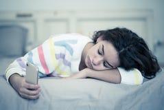 Stående av en borrad, olycklig och trött nätt ung flicka som använder mobiltelefonen i säng royaltyfria foton