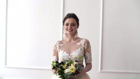 Stående av en brud i bröllopsklänning Elegant brunettbrud med blommor lager videofilmer