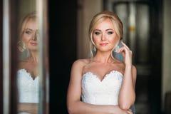 Stående av en brud i en bröllopsklänning Bruden klär i hotellet  Royaltyfria Foton