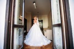 Stående av en brud i en bröllopsklänning Bruden klär i hotellet  Arkivfoton