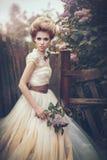 Stående av en brud i en vit klänning med blommor i retro stil Royaltyfria Bilder