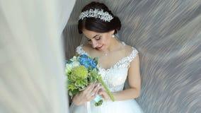 Stående av en brud med en bukett av blommor i hennes händer nära fönstret arkivfilmer