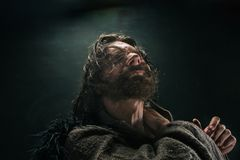 Stående av en brutala flintskalliga viking i en stridpost som poserar mot en svart bakgrund Arkivbild