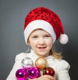 Stående av en charmig liten flicka i jultomten hatt royaltyfri bild