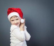 Stående av en charmig liten flicka i jultomten hatt royaltyfria foton