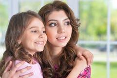 Stående av en charmig liten flicka med den hemmastadda mamman Arkivfoton