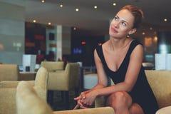 Stående av en charmig lyckad kvinnlig entreprenör som tänker om nya affärsidéer, medan sitta i modern inre arkivbilder
