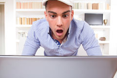 Stående av en chockad manlig student som ser bildskärmen av hans varv Royaltyfria Bilder
