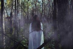 Stående av en död flicka på allhelgonaafton i en dyster skog arkivfoto
