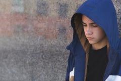 Stående av en deprimerad ledsen tonårs- pojke på en mörk bakgrund, tonårs- problembegrepp arkivbilder